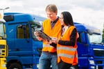 stock-photo-logistics-proud-driver-or-forwarder-and-female-coworker-with-tablet-computer-in-front-of-trucks-165232715